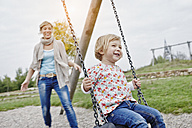 Mother with daughter on swing on playground - RORF00848