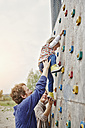 Girl climbing on a wall supported by parents - RORF00854