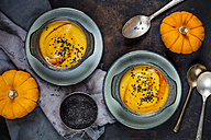 Bowls of creamed pumpkin soup sprinkled with black cumin next to pumpkins - SBDF03203
