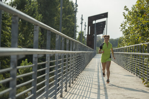 Young woman running on bridge - ZOCF00281