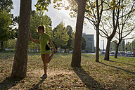 Female athlete stretching in urban park - ZOCF00287
