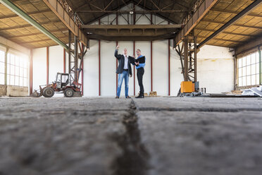 Two businessmen with documents talking in old industrial hall - DIGF02413