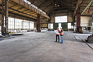 Two men with plan wearing safety vests talking in old industrial hall - DIGF02416