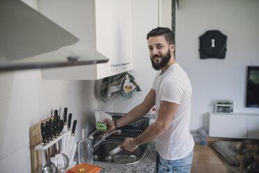 Young man washing dishes - RAEF01875