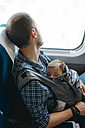 Father on the train holding his sleeping baby in a baby carrier - GEMF01603