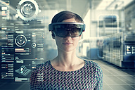 Woman wearing mixed reality smartglasses at transparent screen - RBF05663