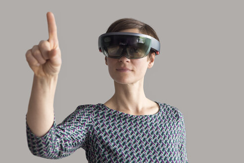 Woman wearing mixed reality smartglasses raising her hand - RBF05666