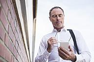 Businessman at brick wall using cell phone - DIGF02444