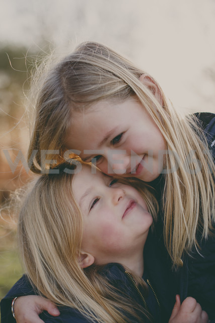 Two cute blond sisters cuddling outdoors - NMSF00082