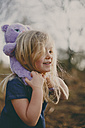 Smiling girl carrying a teddy outdoors - NMSF00091