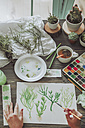 Young woman painting plants with water colors - RTBF00855