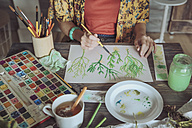 Young woman painting plants with water colors - RTBF00858