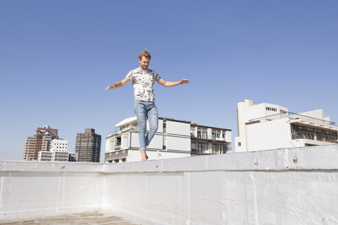 Barefooted man balancing on balustrade of a rooftop terrace - WESTF23068