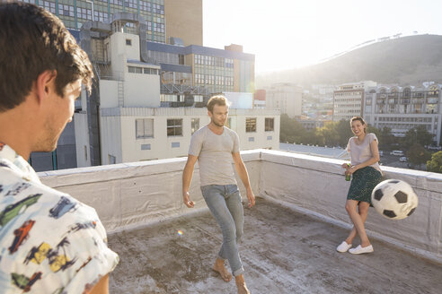 Friends meeting on rooftop terrace in summer, playing football - WESTF23071