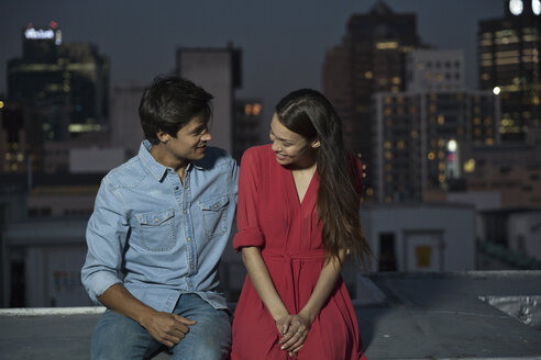 Young couple flirting at a rooftop party - WESTF23080