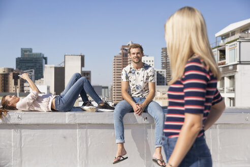 Friends meeting on a rooftop terrace in summer, woman using smartphone - WESTF23083
