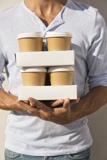 Young man carrying stacks of take away coffee - WESTF23092