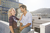 Young couple flirting on a rooftop terrace - WESTF23098