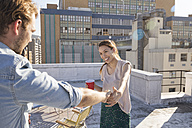 Young couple celebrating on a rooftop terrace, dancing together - WESTF23110