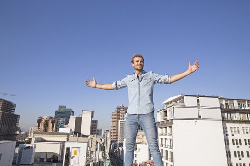 Young man standing on rooftop terrace with arms outstretched - WESTF23113