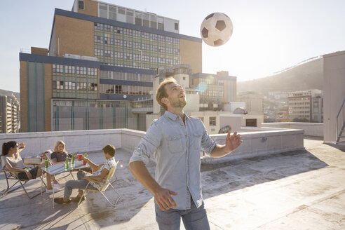 Friends meeting on rooftop terrace in summer, playing football - WESTF23122