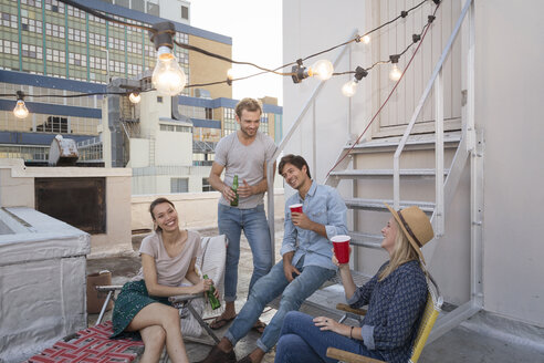 Friends having a rooftop party on a beautiful summer evening - WESTF23134