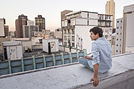 Young man sitting on balustrade of a rooftop terrace, looking at view - WESTF23146