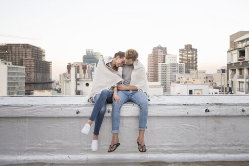 Romantic couple sitting on rooftop terrace, enjoying the view - WESTF23149