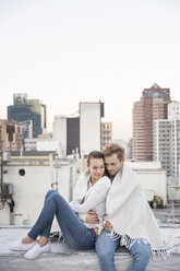 Romantic couple sitting on rooftop terrace, enjoying the view - WESTF23152