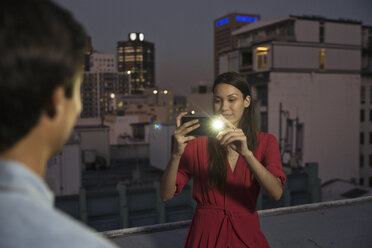 Young woman taking pictures of friends at a rooftop party - WESTF23158
