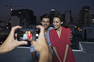 Young man taking picture of a couple at a rooftop party - WESTF23161