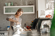Woman at home in kitchen pouring coffee into cup - JOSF00769