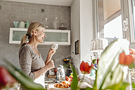Happy woman at home in kitchen looking out of window - JOSF00772