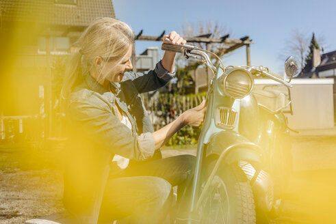 Smiling woman with vintage motorcycle - JOSF00775