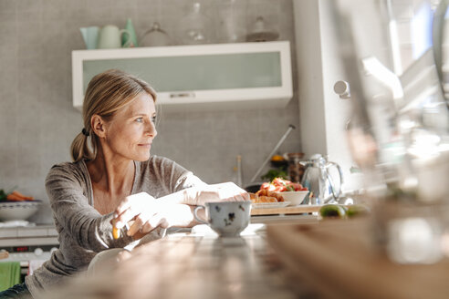 Woman at home in kitchen looking out of window - JOSF00781