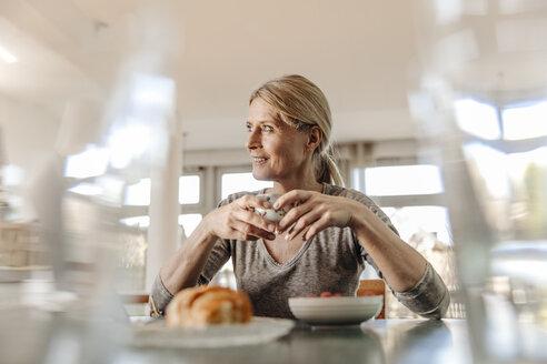 Woman at home sitting at table having breakfast - JOSF00790