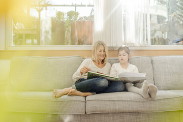 Mature woman and girl at home looking at photo album on couch - JOSF00796