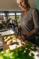 Woman in kitchen cutting limes and kiwis - JOSF00802
