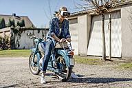 Woman sitting backwards on vintage motorcycle wearing VR glasses - JOSF00808
