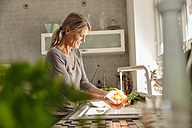 Woman in kitchen washing tomatoes - JOSF00811