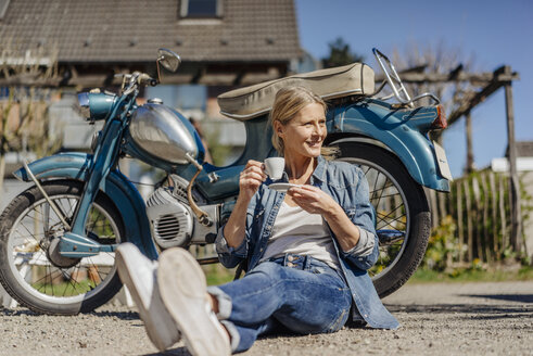 Smiling woman sitting at vintage motorcycle having a coffee break - JOSF00814