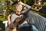 Woman with cup of coffee relaxing on garden bench - JOSF00817