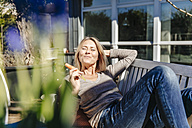Woman relaxing on garden bench eating a carrot - JOSF00820