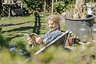 Smiling woman reading book on garden bench - JOSF00823