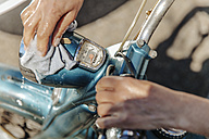 Close-up of woman cleaning vintage motorcycle - JOSF00826