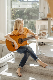 Smiling woman at home with guitar - JOSF00829