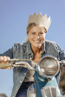 Smiling woman on vintage motorcycle wearing a crown - JOSF00832