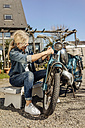 Woman cleaning vintage motorcycle - JOSF00835