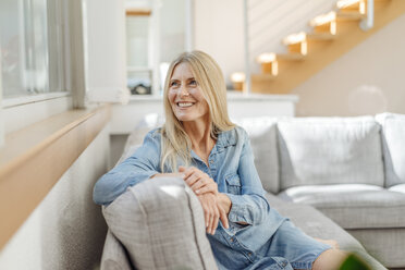 Smiling woman at home sitting on couch - JOSF00844