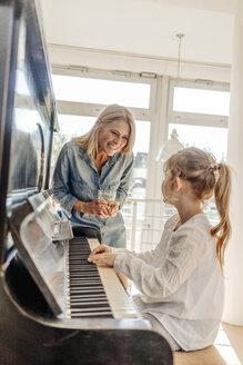 Happy mature woman looking at girl at the piano - JOSF00889